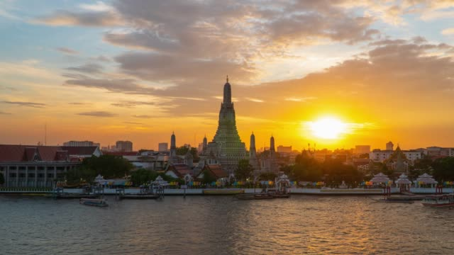 zoom in: sunset to night timelapse at wat arun temple in bangkok, thailand. - fiume chao phraya video stock e b–roll