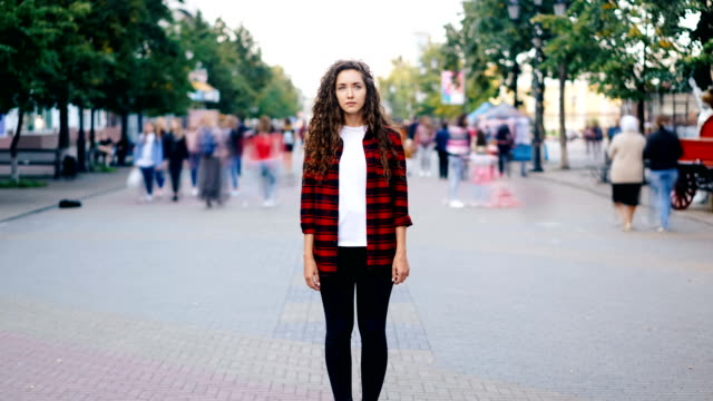 zooma in time-lapse av vacker flicka med långt lockigt hår står i gatan tittar på kameran när många män och kvinnor vandrar runt i hast sommardag. - stationär bildbanksvideor och videomaterial från bakom kulisserna