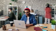istock Zoom in time-lapse of creative guy working in office using laptop at desk 1150438235