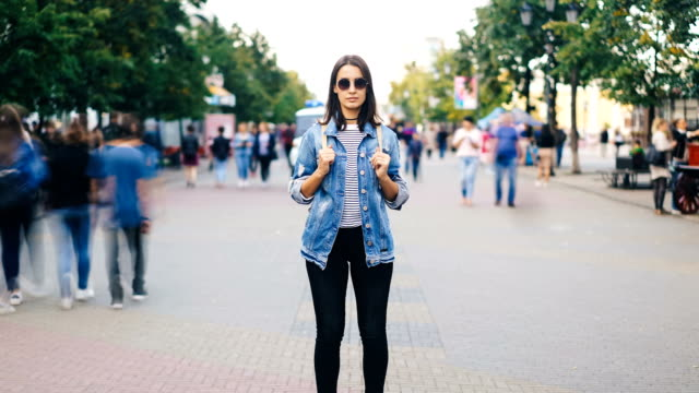 Zoom in time-lapse of female traveler standing in the street with backpack wearing sunglasses and casual clothing and looking at camera when men and women are rushing around. Zoom in time-lapse of female traveler standing alone in the street with backpack wearing sunglasses and casual clothing and looking at camera when men and women are rushing around. individuality stock videos & royalty-free footage