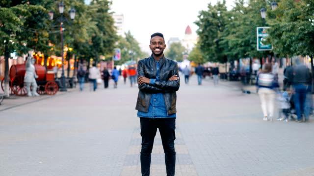 zooma in time-lapse av glad african american kille klädd i jeans och skinnjacka står ensam i street downtown, leende och tittar på kameran med publiken flytta genom. - stationär bildbanksvideor och videomaterial från bakom kulisserna