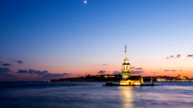 Zoom in timelapse of Maiden Tower or Kiz Kulesi with floating tourist boats on Bosphorus in Istanbul at night video