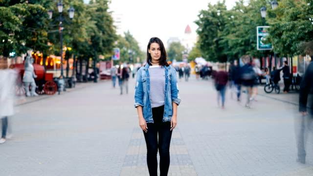 zooma in time-lapse av söt flicka i trendiga kläder tittar på kameran stående på gågata själv när upptagna män och kvinnor flyttar runt. - stationär bildbanksvideor och videomaterial från bakom kulisserna
