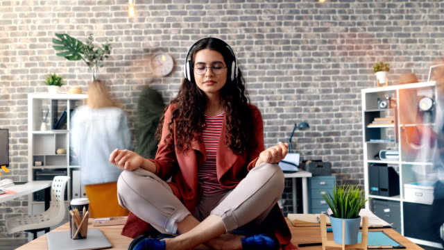 Zoom in time-lapse of woman listening to music in lotus pose on office desk Zoom in time-lapse of young woman listening to music through headphones sitting in lotus pose on office desk relaxing enjoying break. Youth and relaxation concept. lotus position stock videos & royalty-free footage
