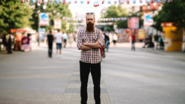Zoom in timelapse of Young bearded man standing still at sidewalk in crowd traffic with people moving fast video