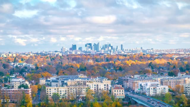 Zoom in to skyscrapers of Paris business district La Defense. Timelapse at a sunny autumn day with blue cloudy sky. From Saint-Germain-en-Laye, west of Paris, France