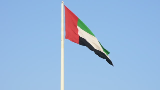 zoom in view of a united arab emirates flag flying and waving in the sunshine with a deep blue sky background. - uae flag filmów i materiałów b-roll