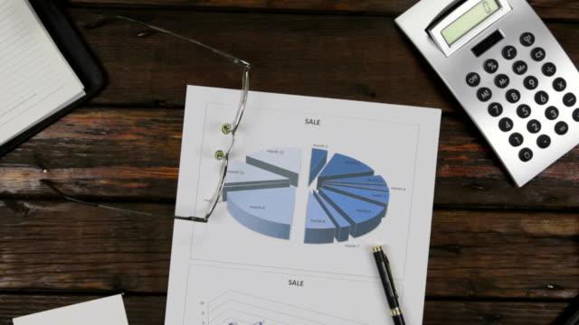 Zoom, bureau se concentrer sur un verre et un stylo, couché sur un graphique. Crane abattu. Image conceptuelle de la collecte de données et du travail statistique. - Vidéo