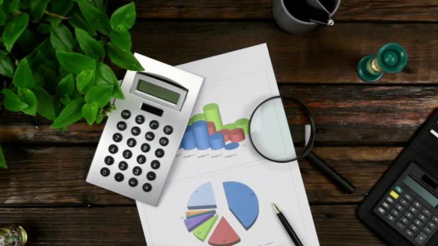 Zoom. Bureau de bureau, concentrez-vous sur le graphique, la calculatrice et la loupe. Vue d'en haut. - Vidéo