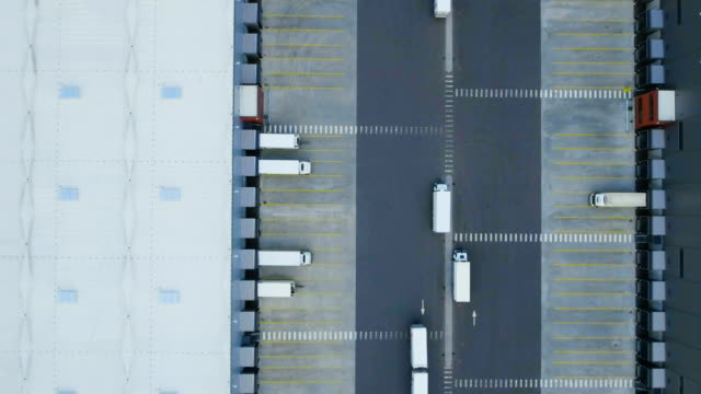 Zoom Out Aerial Shot of Industrial Warehouse/ Storage Building/ Loading Area where Many Trucks Are Loading/ Unloading Merchandise. Zoom Out Aerial Shot of Industrial Warehouse/ Storage Building/ Loading Area where Many Trucks Are Loading/ Unloading Merchandise. Shot on RED EPIC-W 8K Helium Cinema Camera. warehouse aerial stock videos & royalty-free footage