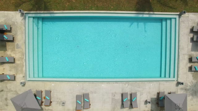 Zoom out from clear turquoise water of swimming pool video