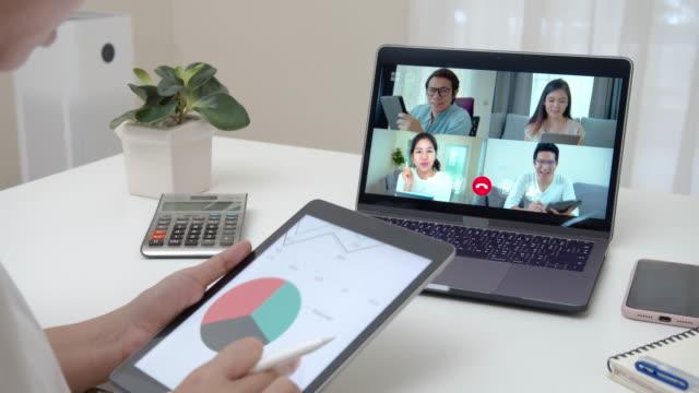 stockvideo's en b-roll-footage met zoom uit van de zakenvrouw praten over verkoop verslag in video conferentie. aziatisch team dat laptop en tablet online vergadering in videogesprek gebruikt. werken vanuit huis, werken op afstand en self isolatie. - ver