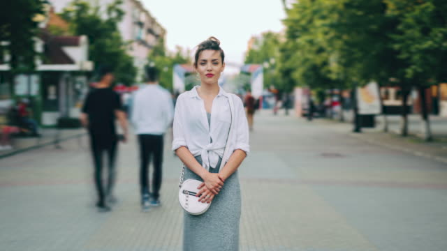 Zoom out of good-looking young lady standing alone on street looking at camera Zoom out of good-looking young lady standing alone on busy city street looking at camera while crowd of pedestrians in passing by. People and lifestyle concept. individuality stock videos & royalty-free footage