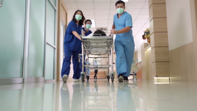 vídeos de stock e filmes b-roll de 4k uhd zoom out point of view low angle shot: patient on hospital gurney stretcher bed being transported down the hospital hallway by the medical team. - empurrar atividade física
