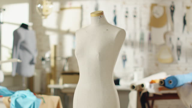 Zoom Out Shot of a Tailoring Mannequin that Stands in a Bright and Sunny Studio. Various Sewing Items and Colourful Fabrics Laying around, Mannequins Standing, and Sketches Pinned to the Wall. video