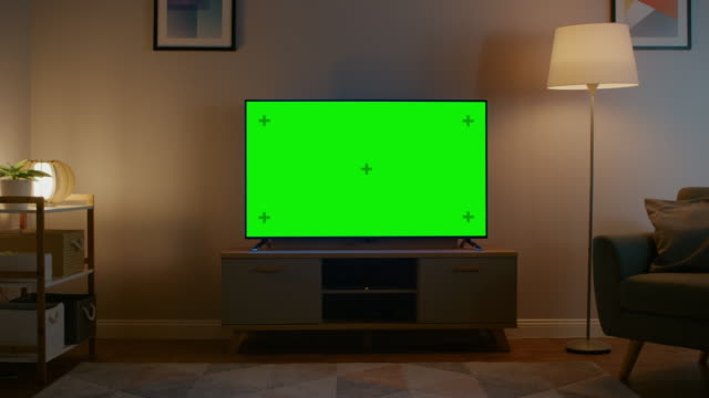 Zoom Out Shot of a TV with Horizontal Green Screen Mock Up. Cozy Evening Living Room with a Chair and Lamps Turned On at Home.