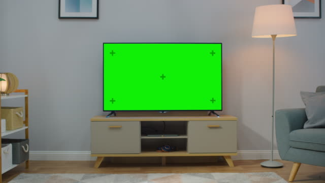 Zoom Out Shot of a TV with Horizontal Green Screen Mock Up. Cozy Living Room at Day Time with a Chair and Lamps Turned On at Home.