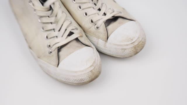 vídeos de stock e filmes b-roll de zoom out shot of dirty white shoes - cheiro desagradável