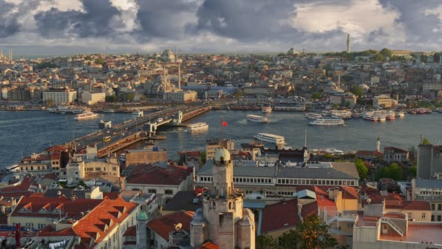 Zoom out shot of Istanbul, Turkey. Sunset view of Istanbul city center from Galata tower. Ferries sail along the Golden Horn Bay near the Galata Bridge