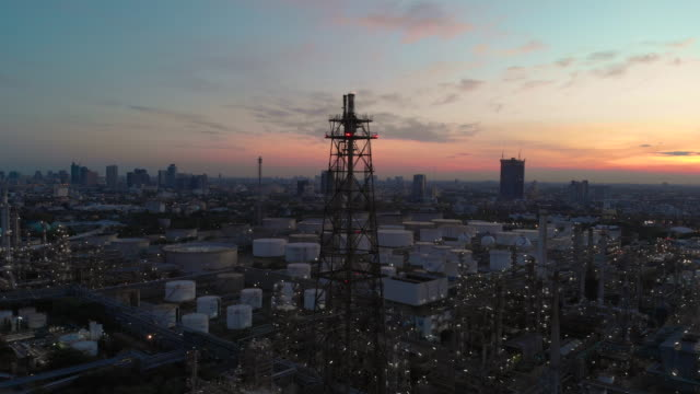 Zoom out: Smoke stack of Oil refineries at twilight