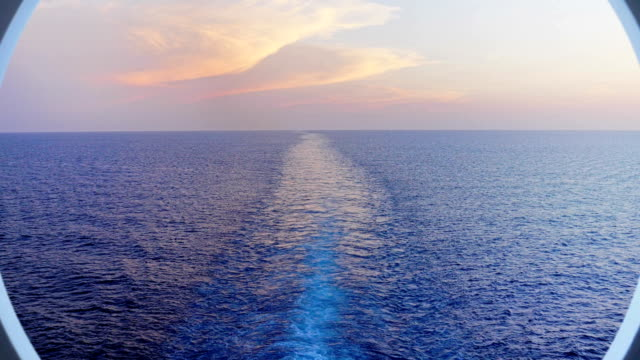 zoom out through cruise ship's porthole over rear wake - cruise video stock e b–roll