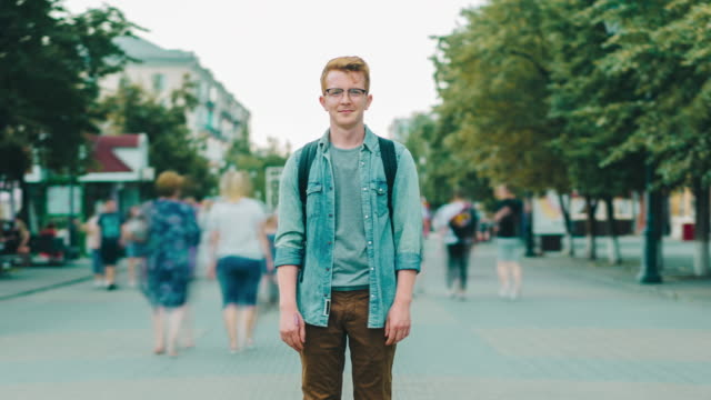Zoom out time lapse of attractive male student in pedestrian city street Zoom out time lapse of attractive male student standing in pedestrian city street looking at camera while men and women are rushing around. People and life concept. redhead stock videos & royalty-free footage