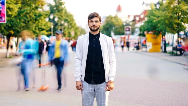 zooma ut time-lapse av attraktiv kille står på trånga gata i staden och tittar på kameran sommardag medan människor är flyttar runt. liv och ensamhet koncept. - zoom ut bildbanksvideor och videomaterial från bakom kulisserna