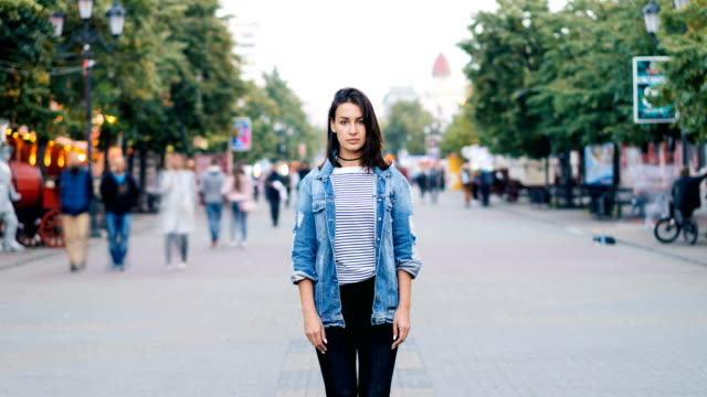 zoom out time-lapse of beautiful lady with dark hair standing alone among crowd of people and looking at camera. modern life, society and loneliness concept. - спокойствие стоковые видео и кадры b-roll