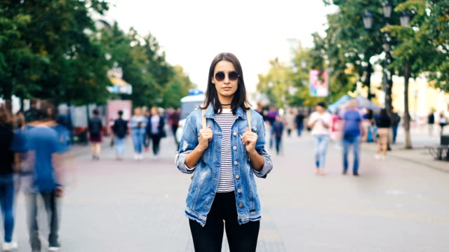 Zoom out time-lapse of confident young lady in sunglasses looking at camera standing in busy pedestrian street in flow of people. Youth and society concept.