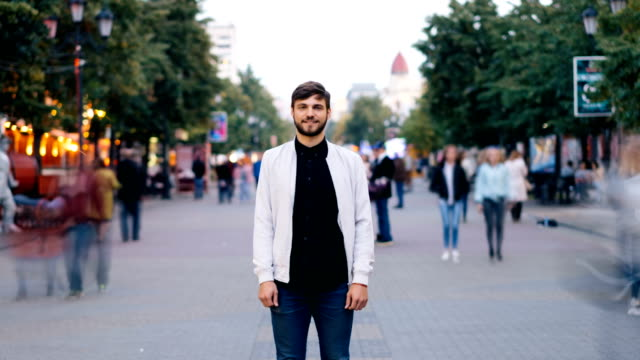 zoom out time-lapse of confident young man looking at camera standing in city center in pedestrian street while men and women are walking around him in hurry. - спокойствие стоковые видео и кадры b-roll