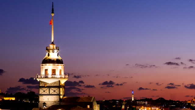 Zoom out timelapse of Maiden Tower or Kiz Kulesi with floating tourist boats on Bosphorus in Istanbul at night video