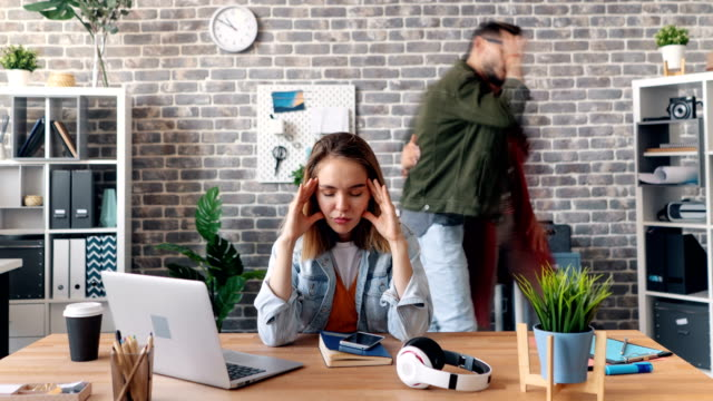 Zoom out time-lapse of tired young woman touching head in office feeling sick