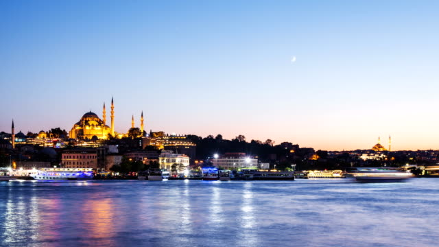 Zoom out Timelapse view of Istanbul cityscape with Suleymaniye mosque with tourist ships floating at Bosphorus at night video