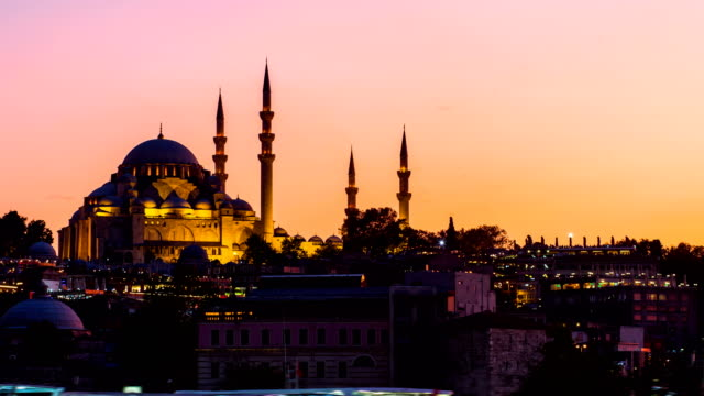 Zoom out Timelapse view of Suleymaniye mosque with tourist ships floating at Bosphorus in Istanbul at night video