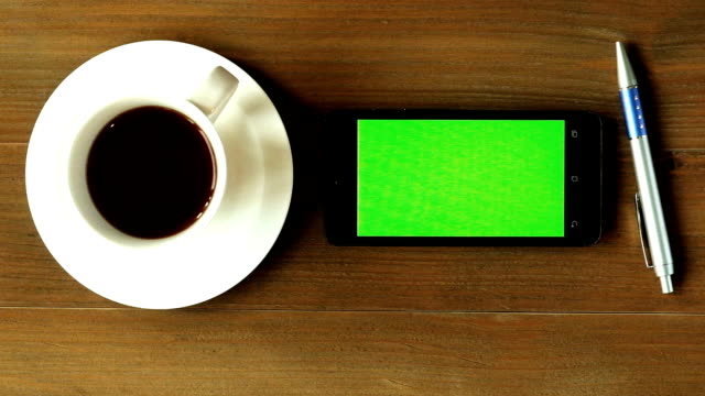 Zoom out , Top view green screen smart phone working at wood table with coffee and pen video
