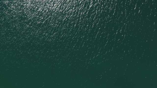 Zoom Out Turning Above Blue Atlantic Ocean Water. High Angle Aerial View