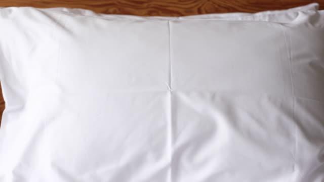 vídeos y material grabado en eventos de stock de alejar la almohada blanca en cama en el dormitorio - almohada