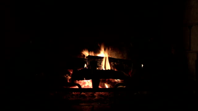 Zoom wood fire in brick fireplace with glowing fish decorations video