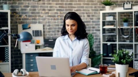 放大漂亮的女人在辦公室使用筆記本電腦,然後看著相機微笑 - laptop 個影片檔及 b 捲影像