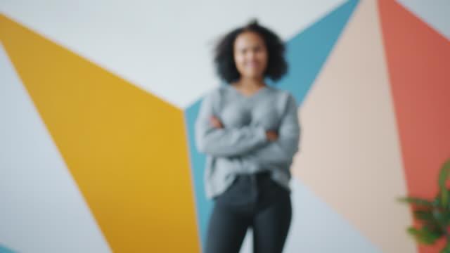 vídeos de stock e filmes b-roll de zoom-in portrait of attractive african-american girl standing indoors smiling - desfocado focagem