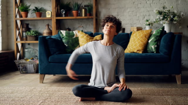 zoom-in portrait of good-looking girl stretching arms and twisting body then relaxing after yoga practice in easy lotus position. leisure and interior concept. - mindfulness stock videos & royalty-free footage