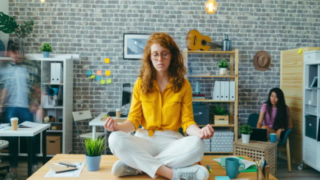 Zoom-in time lapse of pretty girl meditating on desk in office enjoying break Zoom-in time lapse portrait of pretty girl meditating on desk in office enjoying break sitting in lotus pose with closed eyes. Relaxation and business concept. lotus position stock videos & royalty-free footage