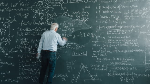 Zoom-in time lapse of senior man scientist writing calculations on blackboard Zoom-in time lapse of senior man scientist writing calculations on blackboard wall in class busy with science. Profession, clever people and intelligence concept. genius stock videos & royalty-free footage