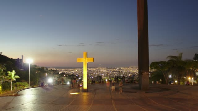en zoomning dag till natt övergångstid förfaller från praça do papa, ett mycket populärt torg för fritid i belo horizonte, huvudstad i minas gerais staten i brasilien. - krucifix bildbanksvideor och videomaterial från bakom kulisserna