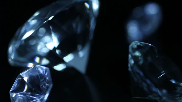 Zooming in and out of huge diamonds Slowly zooming in and out of huge diamonds, short halts at diferent gems. Low key shot with small depth of field, isolated on black. Full HD 1080 clip without sound, 16 seconds. diamond stock videos & royalty-free footage