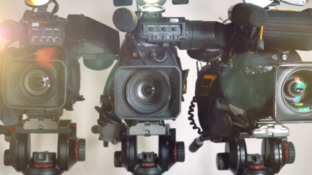 A zooming out shot on three brightly lit video cameras. video