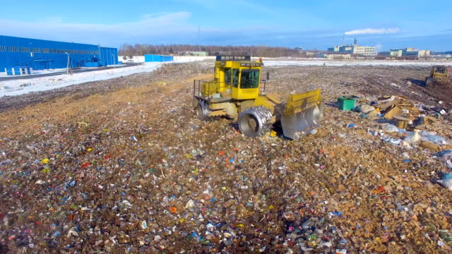 A zooming out view on a landfill compactor. video