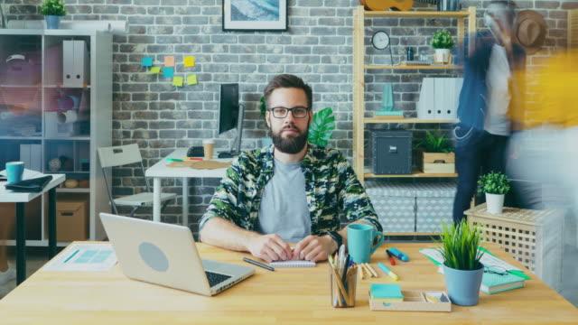 zooma ut tid förflutit attraktiv kille med allvarliga ansikte arbetar i office - skägg bildbanksvideor och videomaterial från bakom kulisserna